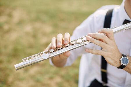 young man playing a clarinet or flute. flutist musician