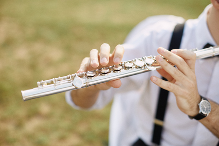 professional flute: young man playing a clarinet or flute. flutist musician