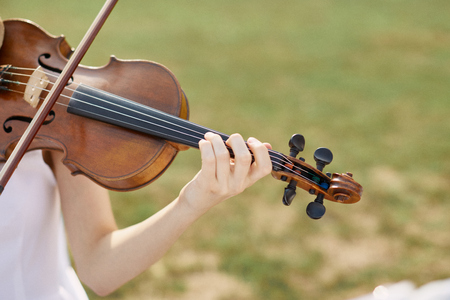 violinista: Violinist woman. Young woman playing a violin outside.