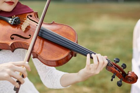 Violinist woman. Young woman playing a violin outside.