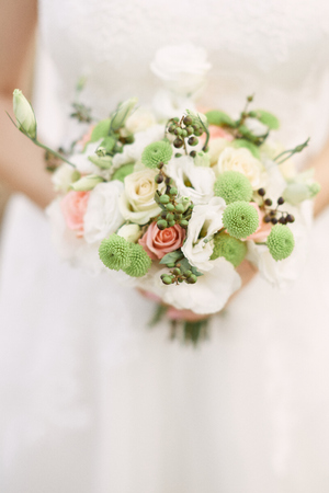 Bridal bouquet. Beautiful bouquet of different colors in the hands of the bride
