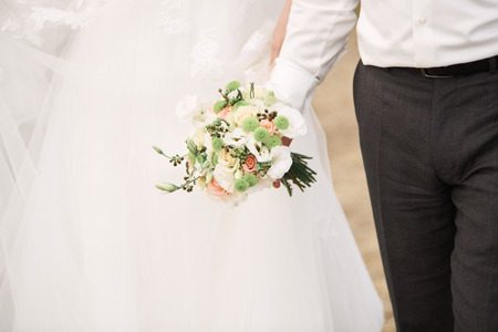 Bridal bouquet. Bride and groom holding hands. Wedding day.