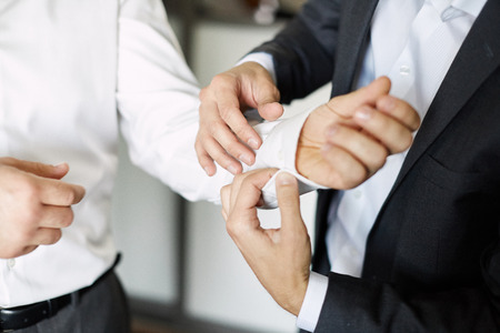 groom getting ready dressed in the morning. buttons in white shirt Stock Photo