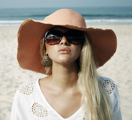 Beautiful blonde woman on the beach in the had Foto de archivo