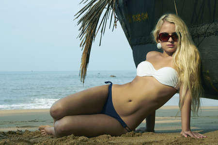 Beauty blond woman on the beach near the boat photo