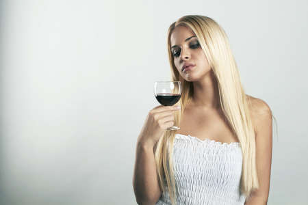 Beauty blond woman in blue dress with glass of red wine Stock Photo - 18594091