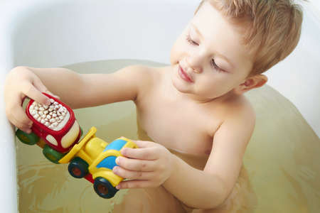 Little boy plays toys in bathroom photo
