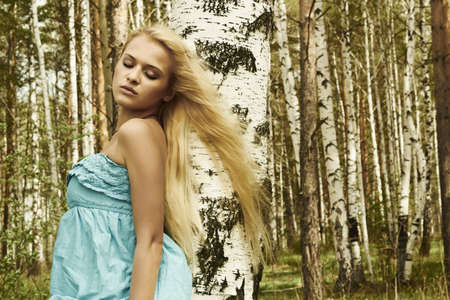 Beautiful blond woman in russian forest  flying hair photo