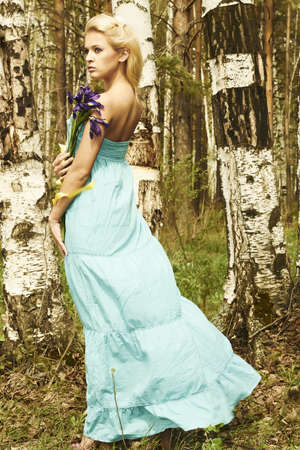 Beautiful blond woman with blue flowers walking in a forest photo