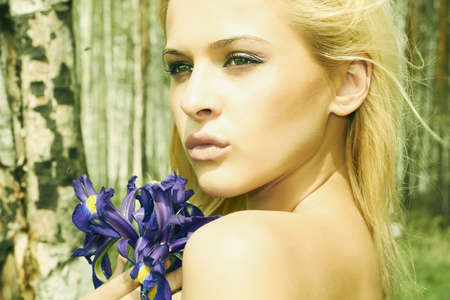 Beautiful blond woman with blue flowers in a forest photo