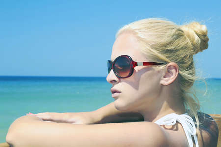 Beautiful blond woman on the beach in sunglasses  sea background photo