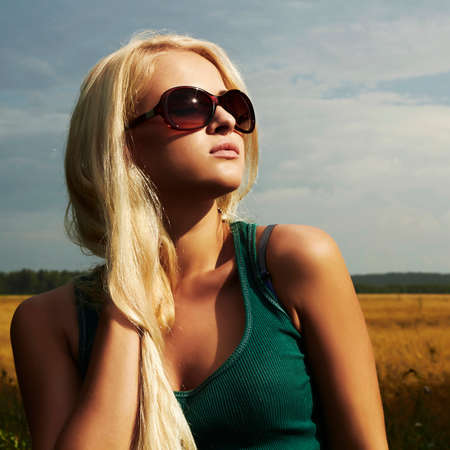 Beautiful blond girl on the field beauty woman sunglasses   nature background