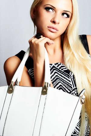 modieuze mooie blonde vrouw met met handtas. winkelen. schoonheid meisje. professionele make-up. stijl. mode Stockfoto