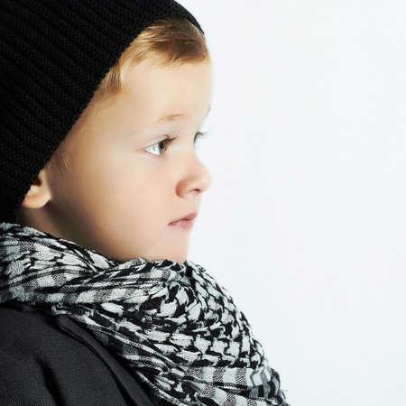 fashionable little boy in scarf and hat.stylish kid. fashion children. black cap. winter style photo