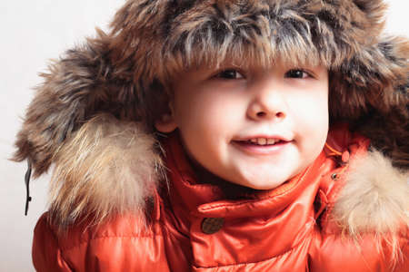 smiling child in a fur hat. fashion kid. winter style. little boy. children. orange winter jacket photo
