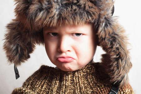 Emotion child in fur hat.fashion.winter style.little boy.children