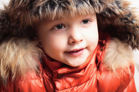 Child in fur hat and orange jacket. fashion kid.children.close-up.winter style photo