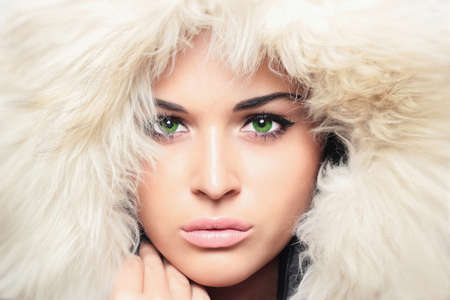 jacked: Fashion portrait of young beautiful woman with fur. white fur hood. winter style