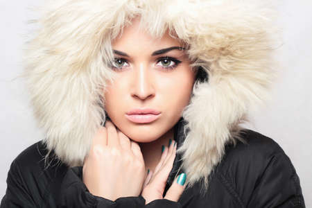 jacked: Fashion portrait of young beautiful woman with fur. hood.pink lips Stock Photo