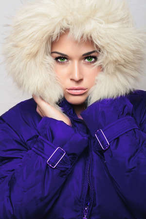 jacked: young beautiful woman with fur. white fur hood. winter style. fashionable girl in blue coat