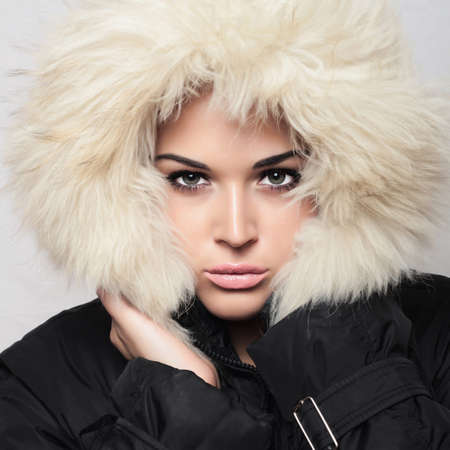 jacked: Fashion portrait of young beautiful woman with fur. hood