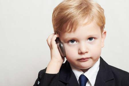 jongen in pak met een mobiele telefoon. blonde knappe kind. modieuze kid Stockfoto