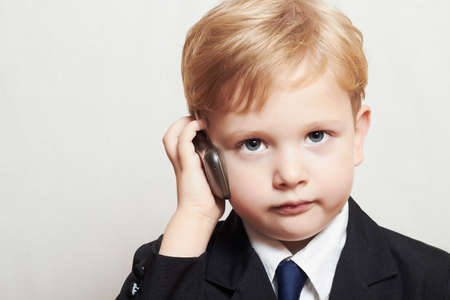 boy in business suit with cell phone. blond handsome child. fashionable kid Standard-Bild