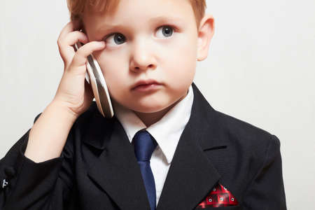 little boy in business suit with cell phone. handsome child. fashionable kid