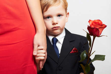child in suit with mother. flower. red dress. family. fashionable little boy. red rose. take the hand photo