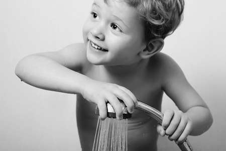 bathed: Smiling little boy is bathed in the shower.