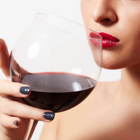 eye red: Beautiful woman drinking red wine Stock Photo