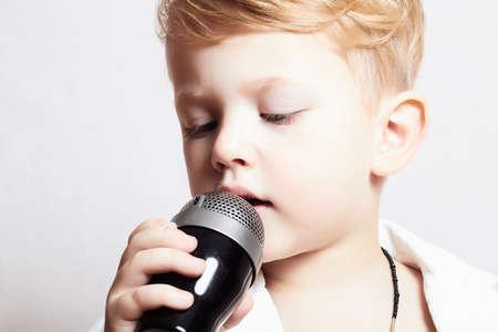niños rubios: niño cantando con micrófono Foto de archivo