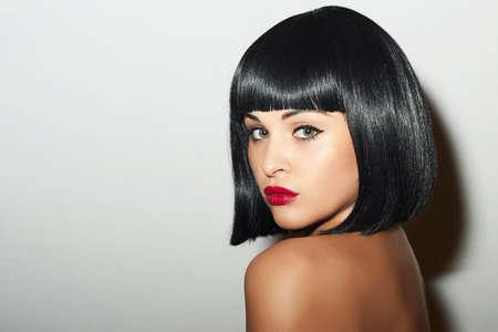 美しいブルネットの少女。健康な黒い髪。ボブのヘアカット。赤い唇。美容女性