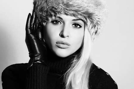 fur: Monochrome portrait of Young Woman in Fur Hat. Beautiful Blond Girl in Black Leather Gloves. Winter Fashion Beauty