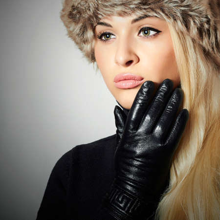 leather gloves: Beautiful Fashion Girl in Fur Hat. Beauty Blond Woman in Leather Gloves. Black sweater. Winter Fashion. Light Background