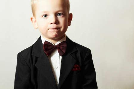 蝶ネクタイでファッショナブルな少年。スタイリッシュな子供。ファッション子供。4 年間黒い服を着て古い子 写真素材