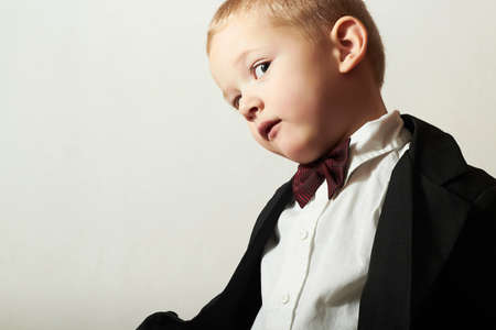 4 years old: Funny Little Boy in Bow tie.Stylish kid. fashion children. 4 Years Old Child in Black Suit Stock Photo