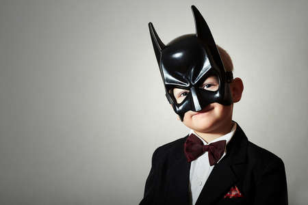 Boy in Mask. Funny Child in Black Suit