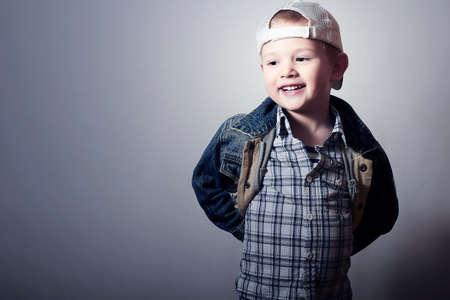Smiling Child. Funny Little Boy in Jeans. Trucker cap. joy. Fashionable Kid 4 years old. plaid shirt. Denim Wear