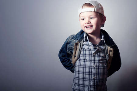 Smiling Child. Funny Little Boy in Jeans. Trucker cap. joy. Fashionable Kid 4 years old. plaid shirt. Denim Wear