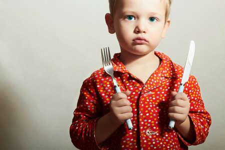 Little Handsome Boy met vork en mes. Hongerig kind. Beauty and Food. Wil eten