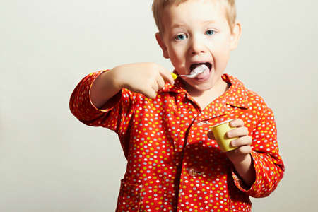 Little Handsome Boy with Yogurt. Hungry Child with Spoon. Open mouth. Enjoy Meal