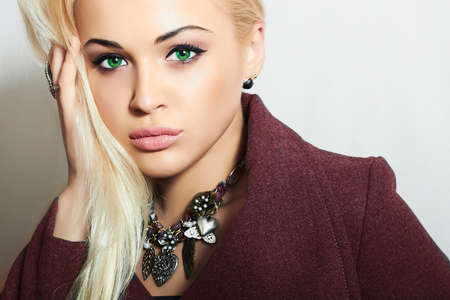 topcoat: Beautiful Blond Woman in Topcoat. Fashionable Lady. Elegance Beauty Girl with Jewelry Stock Photo