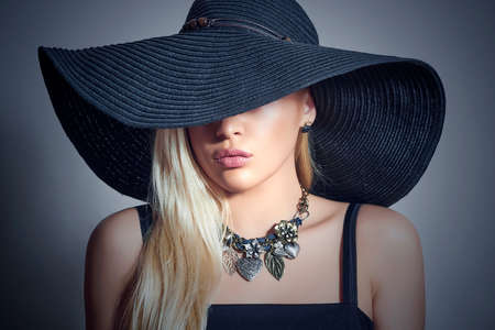black hat: Beautiful Blond Woman in Black Hat. Close-up Portrait. Elegance Beauty Girl. Accessories Stock Photo