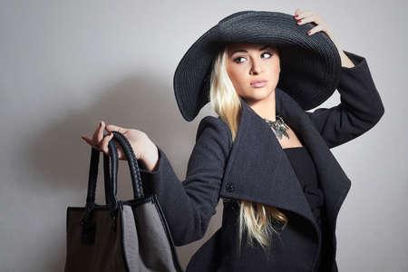 modelos negras: Beautiful Blond Woman in Hat. Fashionable Lady in Topcoat. Elegance Beauty Girl with Handbag.Shopping Foto de archivo