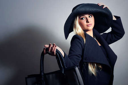 topcoat: Beautiful Blond Woman in Hat. Fashionable Lady in Topcoat. Elegance Beauty Girl with Handbag.Shopping Stock Photo