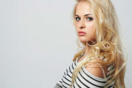 Beautiful woman in sailor dress. Curly hair. Beauty Posing Fashion Blond Girl