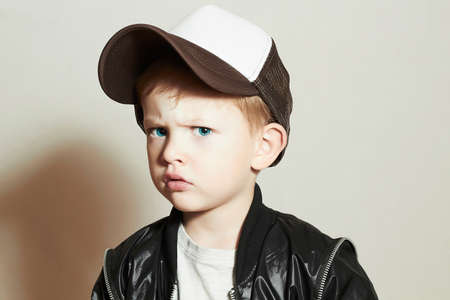 Fashionable little boy.fashion children.handsome blond kid with big blue eyes.Boy in Tracker Hat. Sad Child in Cap