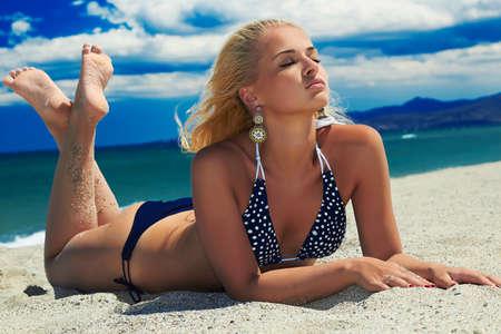 beach model: beautiful sexy woman on the beach. beauty Blond girl in bikini. summer holidays.Blue Sea