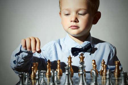 ni�os inteligentes: Ni�o jugando chess.Smart kid.fashion hijos.5 A�os de Edad Child.Little genio Ni�o. Game.Chessboard inteligente Foto de archivo